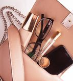 Flat lay of pink leather woman bag open out with cosmetics, acce. Ssories  and smartphone on white background with copy space. Close up Stock Photo