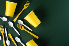 Flat lay plastic and paper utensils on a green background royalty free stock photography