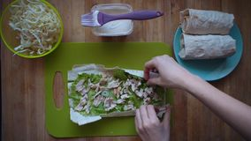 The process of making shawarma with female hands on a wooden table, top view. stock footage