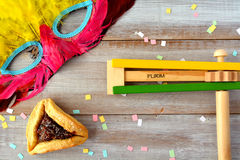 Flat lay of Purim Jewish holiday food and objects. Hamantaschen, wooden Purim gragger and carnival mask. Copy text space Stock Photo