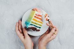 Flat lay of rainbow vegan cake piece in woman`s hands. On grey background stock photography
