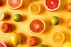 Flat lay the raw fresh citrus fruit - orange, lemon and grapefruit over yellow background. Healthy eating concept. Pattern with raw fresh Citrus fruit - orange stock photography