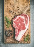 Flat-lay of raw prime beef meat dry-aged steak rib-eye. On bone over rustic wooden board over grey concrete countertop background with seasoning, top view, copy Royalty Free Stock Photo
