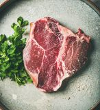 Flat-lay of raw uncooked dry-aged t-bone prime beef steak. Flat-lay of raw uncooked dry-aged t-bone prime beef meat steak with fresh green parsley and smoked Royalty Free Stock Photography