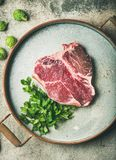 Flat-lay of raw uncooked dry-aged t-bone prime beef steak. Flat-lay of raw uncooked dry-aged t-bone prime beef meat steak with fresh green parsley and smoked Stock Photo