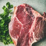 Flat-lay of raw uncooked dry-aged t-bone prime beef steak. Flat-lay of raw uncooked dry-aged t-bone prime beef meat steak with fresh green parsley and smoked Stock Image