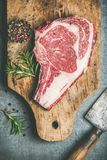 Raw beef steak rib-eye on board with seasoning, top view Royalty Free Stock Photo