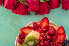 Flat-lay of red flowers roses and beautiful delicious sweet cake with berries on a green table. stock image
