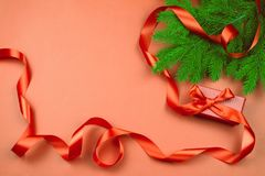 Flat lay with red gift box, red ribbon and Christmas tree branch on red background. Stock Photos