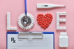 Flat lay of red heart shape of medicine pills and doctor equipment on pink background. royalty free stock images