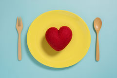 Flat lay of red heart on yellow plate with fork on pastel blue color background Stock Image