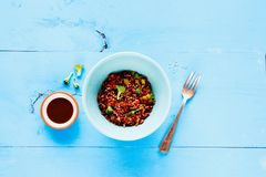 Rice and broccoli bowl. Flat lay of red rice and broccoli bowl. Vegetarian, healthy, diet food concept. On light blue wooden table, top view Royalty Free Stock Photography