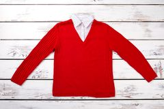 Flat lay red woolen sweater pullover. White wooden background top view Stock Image