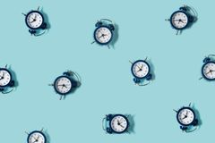 Flat lay retro beautiful new alarm clock on blue color background. Pattern. Top. View Stock Image