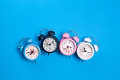 Flat lay retro beautiful new alarm clock on blue paper pastel co. Lor background Stock Photo