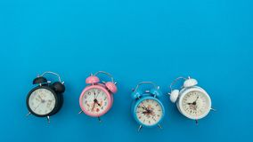 Flat lay retro beautiful new alarm clock on blue paper pastel co. Lor background Stock Photos