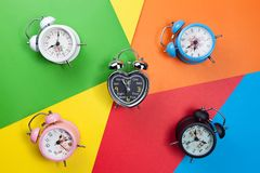 Flat lay retro beautiful new alarm clock on colorful paper paste. L color background Stock Photo