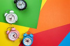Flat lay retro beautiful new alarm clock on colorful paper paste. L color background Stock Image