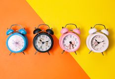 Flat lay retro beautiful new alarm clock on sweet colorful paper. Pastel color background Royalty Free Stock Photography