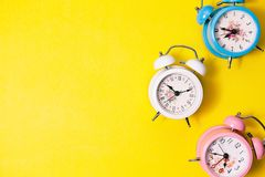 Flat lay retro beautiful new alarm clock on sweet colorful paper. Pastel color background Stock Photos
