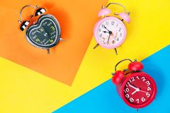 Flat lay retro beautiful new alarm clock on sweet colorful paper. Pastel color background Stock Images