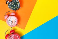 Flat lay retro beautiful new alarm clock on sweet colorful paper. Pastel color background Stock Photography