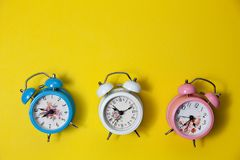 Flat lay retro beautiful new alarm clock on yellow paper pastel. Color background Stock Images