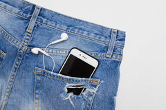 Flat lay of ripped denim shorts with telephone and headphones in Stock Photography