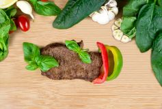 Flat lay of roasted beef steak served with fresh herbs, vegetabl. Roasted beef steak served with fresh spinach, tomatoes, basil, capsicum and garlic on a wooden Royalty Free Stock Photos