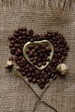 Flat lay of roasted coffee beans on a tablecloth with a golden heart shaped saucer and coffee mug. Cup of morning espresso and pre. Bronze glass vase with Stock Photo