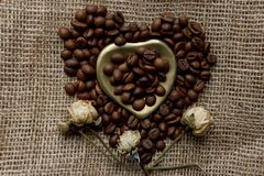 Flat lay of roasted coffee beans on a tablecloth with a golden heart shaped saucer and coffee mug. Cup of morning espresso and pre. Bronze glass vase with Stock Images