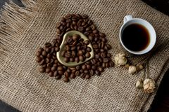 Flat lay of roasted coffee beans on a tablecloth with a golden heart shaped saucer and coffee mug. Cup of morning espresso and pre. Bronze glass vase with Stock Photos
