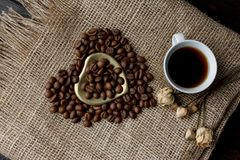 Flat lay of roasted coffee beans on a tablecloth with a golden heart shaped saucer and coffee mug. Cup of morning espresso and pre. Bronze glass vase with Stock Image