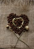 Flat lay of roasted coffee beans on a tablecloth with a golden heart shaped saucer and coffee mug. Cup of morning espresso and pre. Bronze glass vase with Royalty Free Stock Images