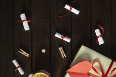 Flat lay romantic background. Gift box with rolled wishes paper gift pack on wooden board. Flat lay romantic background. Top view to giftbox with rolled wishes royalty free stock photography