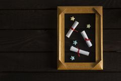 Flat lay romantic background. Giftbox, rolled wish papers, and wooden frame with paper hearts on dark wood board. Flat lay romantic background. Top view to royalty free stock photo