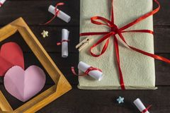 Flat lay romantic background. Giftbox, rolled wish papers, and wooden frame with paper hearts on dark wood board. Flat lay romantic background. Top view to royalty free stock photography