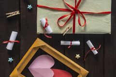 Flat lay romantic background. Giftbox, rolled wish papers, and wooden frame with paper hearts on dark wood board. Flat lay romantic background. Top view to stock photography
