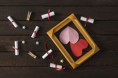 Flat lay romantic background. Giftbox, rolled wish papers, and wooden frame with paper hearts on dark wood board. Flat lay romantic background. Top view to royalty free stock images