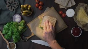 Flat lay of the sandwich with ham and salad on the wooden board in the beam of light, chef`s hand finalizes the sandwich. Making of the fastfood at the kitchen stock video footage