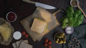 Flat lay of the sandwich with ham and salad on the wooden board in the beam of light, chef`s hand finalizes the sandwich. Making of the fastfood at the kitchen stock video