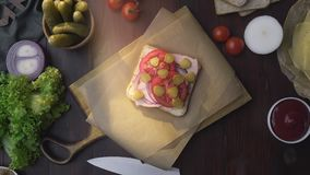 Flat lay of the sandwich with ham and vegetables on the wooden board in the beam of light, making of the fastfood at. Home, meat cooking, at the kitchen, 1080p stock footage