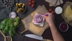 Flat lay of the sandwich with sliced ham and vegetables on the wooden board in the beam of light, chef`s hand adds onion