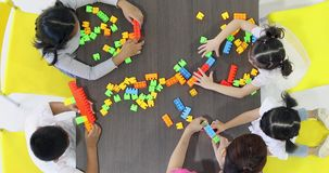 Flat lay scene video of Asian teacher playing colorful build blocks toy with Asian student together,. Concept for classroom stock footage
