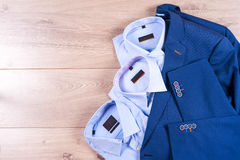 Flat lay set of classic mens clothes such as blue suit, shirts, brown shoes, belt and tie on wooden background. Royalty Free Stock Image