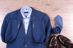 Flat lay set of classic mens clothes such as blue suit, shirts, brown shoes, belt and tie on wooden background. Stock Image