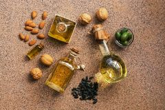 Flat lay a set of different oil in bottles, almond, walnut, sunflower and olive, brown background. View from above.  royalty free stock images