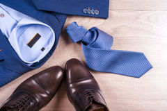 Flat Lay Set Of Classic Mens Clothes Such As Blue Suit, Shirts, Brown Shoes, Belt And Tie On Wooden Background. Royalty Free Stock Photography