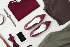 Flat lay set of stylish clothes and accessories. On wooden floor Stock Photos