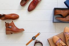 Flat lay set of unopened brown shoes and some brown accessories. Such as belt and watches. Top view Royalty Free Stock Images